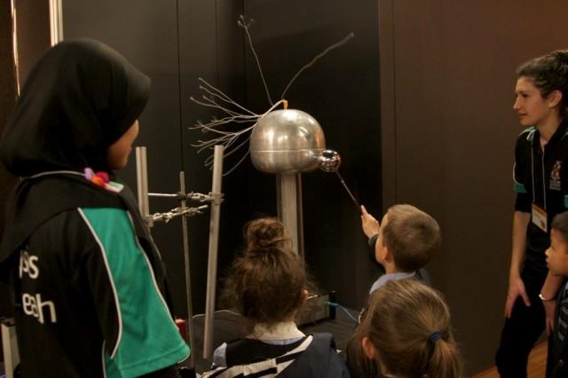Kids playing with the Van de Graaff generator. (Photo Credit: Ana Andres-Arroyo)